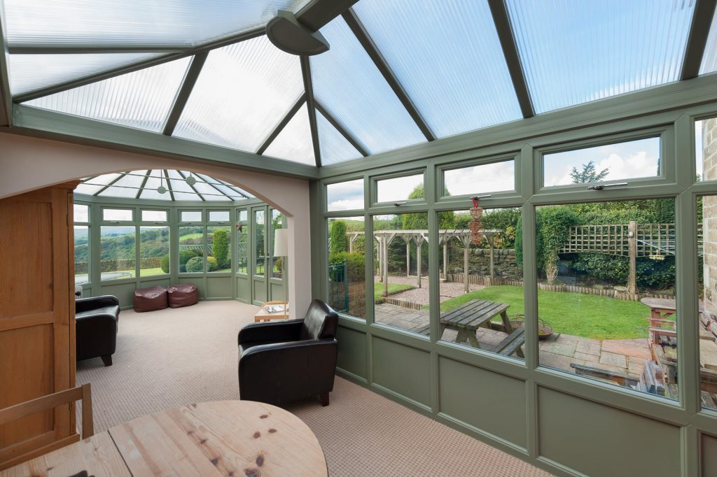Green uPVC casement windows installed within a conservatory