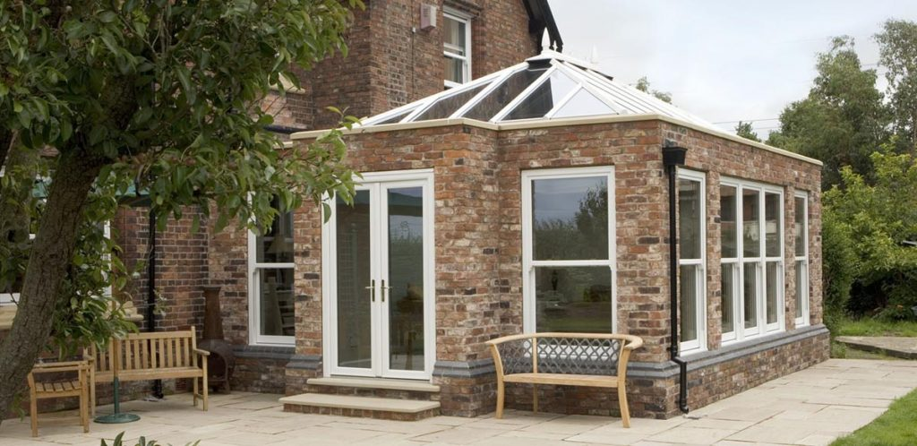 Large brick orangery structure with uPVC windows and roof system