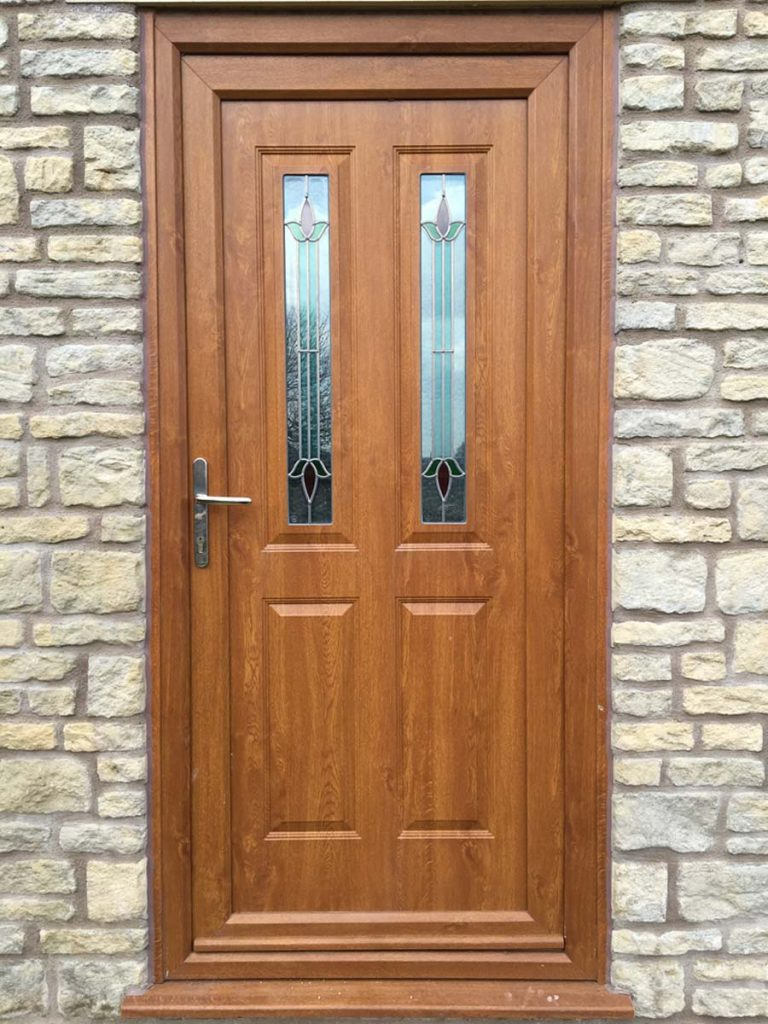 uPVC entrance door in golden oak with decorative glass panels and silver hardware
