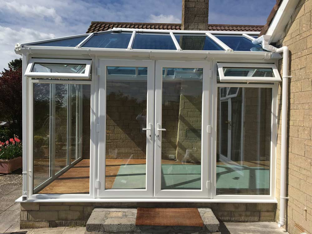 White upvc conservatory with casement windows and french doors